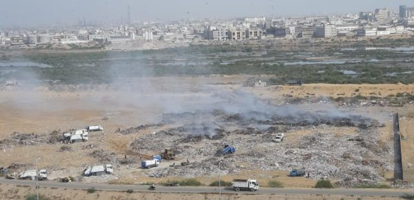 Garbage trucks line up to dump trash at the Malir riverbed. Residents of the area claim that the waste is regularly burned at the site. PHOTO: EXPRESS