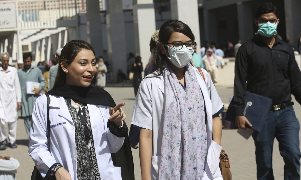 Pakistani doctors wear face masks as they leave the Aga Khan hospital where a patient suspected of having contracted coronavirus was admitted, in Karachi, Pakistan, Thursday, Feb. 27, 2020. (AP Photo/Fareed Khan) — Copyright 2020 The Associated Press. All rights reserved.